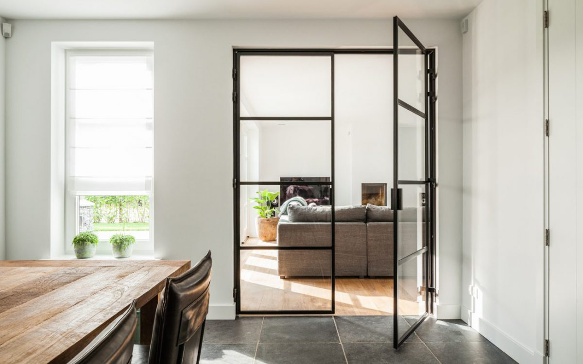 Binnenaanzicht van stalen deuren in keuken naar woonkamer