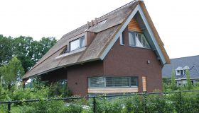 Nieuwbouw van een moderne woning met rieten kap in Haaren